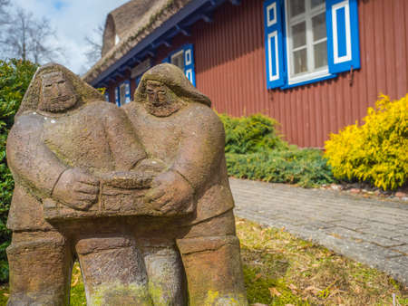 Nida, Lithuania - April 06, 2018: A stone sculpture in front of the red wooden house on a headland in the town of Nida, Curonian Spit 新闻类图片