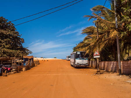 Senegal, Africa - Feb 02, 2019: Old bus the road with red and white sand at the end of the past Paris-Dakar route Stok Fotoğraf - 161466489