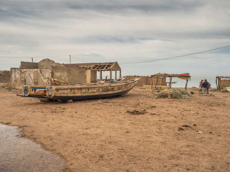 Nianing, Senegal - January 24, 2019: Destroyed wooden fishing boats are standing on a sandy beach in front of an abandoned house in ruins. Africa