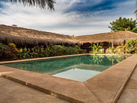 Senegal, Africa - January 24, 2019: African huts with a roof covered with palm leaves around the pool with blue water. Holiday background. Relaxing vacation concept. Senegal Africa.