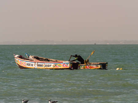 Nianing, Senegal - January 24, 2019: Colorful wooden fishing boats bouncing on the waves anchored far from the beach. africa