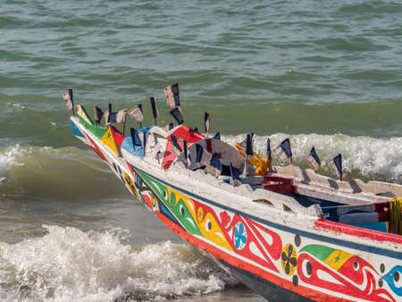 Nianing, Senegal - January 24, 2019: Colorful wooden fisher boat standing on the sandy beach in Senegal. Africa