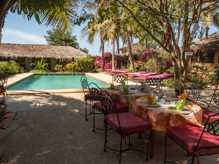 Senegal, Africa - January 2019: A covered table awaits guests next to the pool and African huts with palm leaf roofs. Holiday background. Relaxing vacation concept.