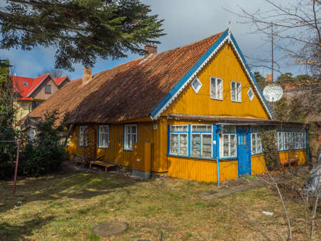 Nida, Lithuania - April 06, 2018: Yellow wooden house on the headland, National Park Curonian Spit, A nature reserve with forests and a long sandy coast, according to a legend made by a giant.