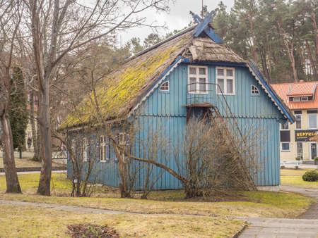 Nida, Lithuania - April 06, 2018: Blue wooden house on the headland, National Park Curonian Spit, A nature reserve with forests and a long sandy coast, according to a legend made by a giant. Stok Fotoğraf - 161466506