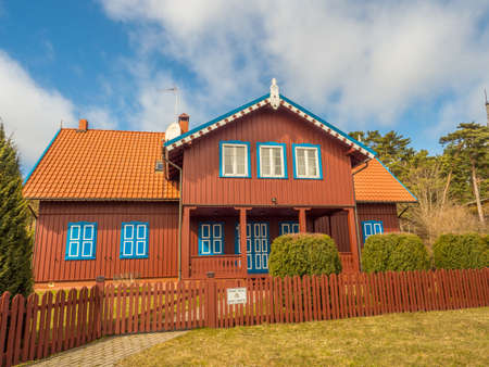 Nida, Lithuania - April 06, 2018: Red wooden house on the headland, National Park Curonian Spit, A nature reserve with forests and a long sandy coast, according to a legend made by a giant. 新闻类图片