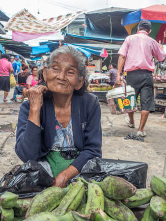 Iquitos, Peru- Mar 27, 2018: Portrait of a woman with a red skin selling bananas on the Belen market, Amazon jungle. South America. Amazonia.