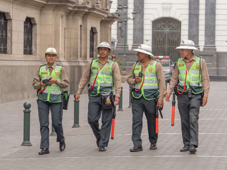 Lima, Peru - December 07, 2018: Group of policemen in straw hats on the streets of Lima. Men and women team. Policia. South America.