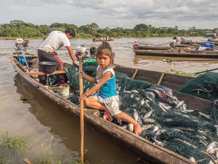 Amazon river, Peru- December 11, 2017: Small peruvian girl is sitting on the wooden boat full of fishes.