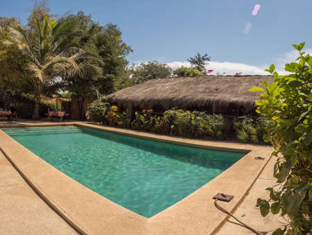 Senegal, Africa - Jan 24, 2019: Huts with a roof covered with palm leaves and deck chairs covered with material in African colors around the pool. Holiday background. Relaxing vacation concept.