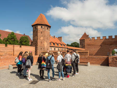 Malbork, Poland - May 22 2019: Tourists looking at Teutonic Castle in Malbork (Marienburg) in Pomerania. Poland. Europe