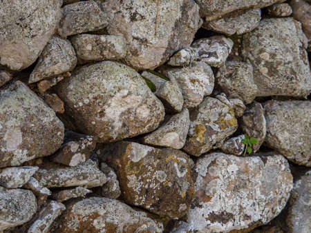 Background. Texture. The wall made of multi-sized stones