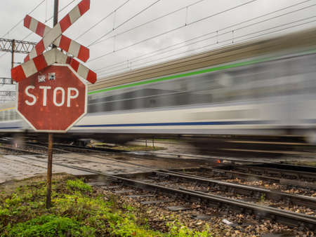 Moving passenger trains at the railway depot in Olszynka Grochowska and red STOP sign with Saint Andrew's Cross 免版税图像