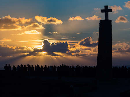 Silhouettes of people and a large cross against the backdrop of a fabulous sunset at the end of Europe, Cabo Da Roca, Portugal