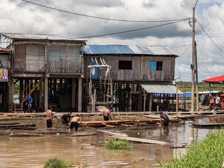 Iquitos, Peru - December 2019: Peruvian men build a footbridge at a flea market during the hight water season- Nanay Market, Amazonia, Latin America Editöryel