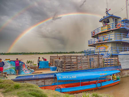 Amazon River, Peru - December 07, 2019: View of slow boat 'Maria Fernanda' and rainbow in the small port on the Amazon River. Amazonia. South America