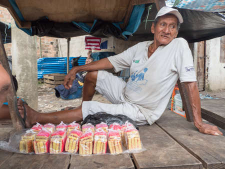Iquitos, Peru - December 2019: Portrait of an old man sitting on the table and selling cakes at the Belen bazaar (Belén market), Iquitos - gate to the rainforest, Amazonia, Loreto, South America