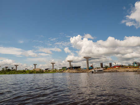 Iquitos, Peru - Dec 2019: Construction of a bridge over the river Nanay - tributary of the Amazon in the city of Iquitos. Amazonia. Latin America.