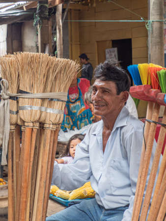 Iquitos, Peru - December 2019: Portrait of a man selling brooms at a Belen bazaar (Belén market), Iquitos - gate to the rainforest, Amazonia, Loreto, South America
