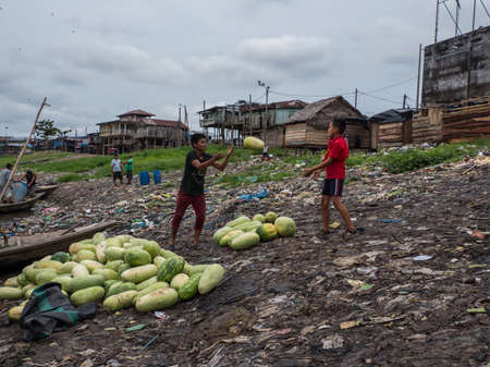 Iquitos, Peru - Sep 2019: Men are shifting fruits from a boat. Enormous pollution can be seen in the background on the banks of the Itaya River. Low Amazon water season. Belén, Amazonia, South America 新闻类图片