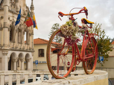 Old, red bike on the fence and a beautiful Town Hall building with the flags of Europe, Portugal and Sintra in the background (Câmara Municipal de Sintra) Grande Lisboa,