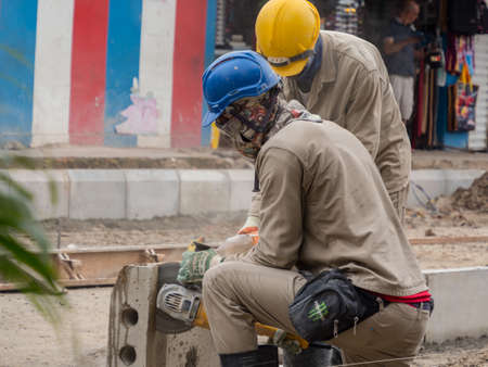 Leticia, Colombia - December 12, 2019: Workers in helmets during the construction of a new road in a small town in the Amazon on the border of the three states of Colombia, Brazil and Peru. Amazonia South America. Tres fronteras area.