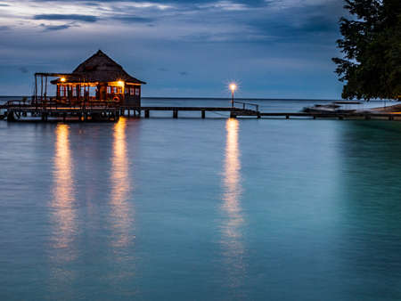 Ora Beach, Indonesia - February 14, 2018: Houses on the water in Ora Beach Resort, Night time. Seram Island, Central Maluku, Indonesia 免版税图像
