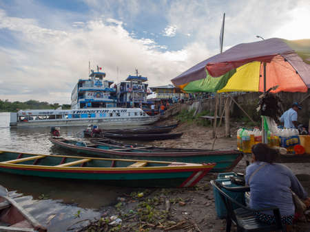 Caballococha, Peru - May 04, 2016: Ferry boats and other small wooden boats in the port in a small town on the bank of the Amazon River, Amazonia, South America.