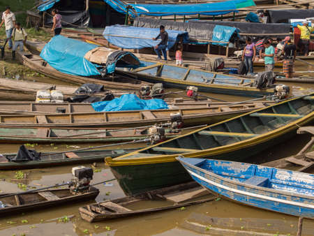 Caballococha,, Peru - May 11, 2016: Many traditional, indian boats on the bank of the river. Amazonia. South America. 新闻类图片