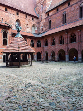 Malbork, Poland - May 22 2019: The well with the pelican's figure on the roof, a symbol of the Teutonic Order in the inner courtyard of the high castle. Medieval Teutonic castle in Malbork, (Marienburg) in Pomerania. Poland. Europe