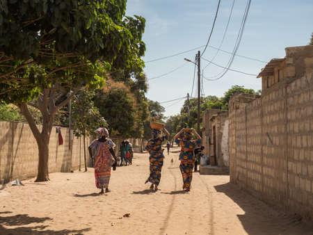 Senegal, Africa - Jan, 2019: Women in a traditional costume called 'boubou' walking along the street.