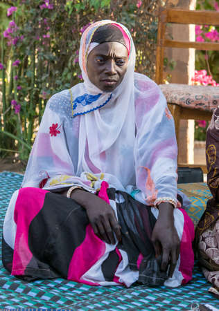 Senegal, Africa - Jan, 2019: Portrait of a beautiful Senegalese woman in a traditional costume called 'boubou' and a swing on her head