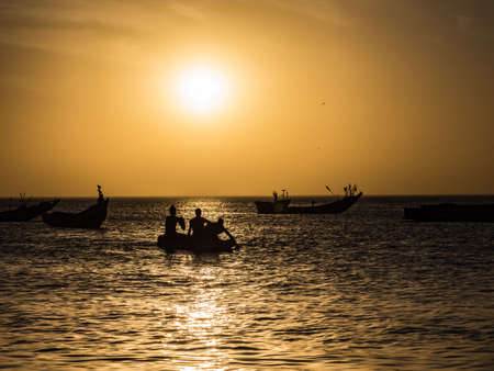 Sunset on the Atlantic coast in Africa and the silhouettes of a fishing boats on the water, Senegal, Africa