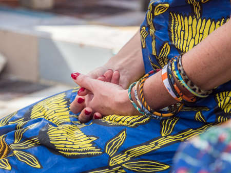Well-groomed hands of a white woman against the background of a traditional African costume called