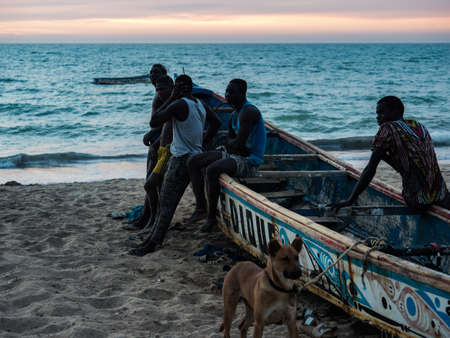 Senegal, Africa - January 2019: African boys sitting on a boat on a sandy beach about watching wrestling training. Senegal wrestling is a national sport in Senegal. Africa.
