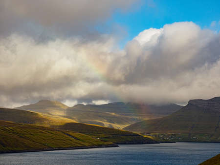 Beautiful panoramic view with the rainbow during golden hours for to the peaks of Eysturoy Island. Faroe Islands. Denmark. Northern Europe