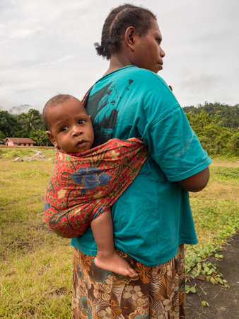 Kensi, Indonesia - February 01, 2018: A child from the Mairasi tribe carried on his mother's back in a colorful swing, Kensi village, Bird's Head Peninsula, West Papua, Papua Barat, Asia.
