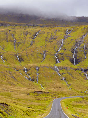 Dozens of small rivulets flowing down the rocks after a rainy day in the Faroe Islands. Denmark, Northern Europe. 免版税图像