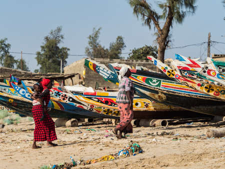 Nianing, Senegal - January 24, 2019: Senegalese woman and chid the background of colorful wooden fishing boats standing on the sandy beach in Senegal. Africa 新闻类图片
