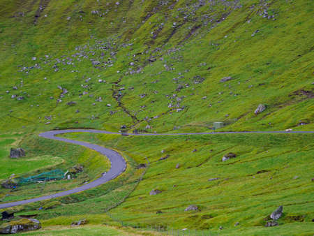A winding dirt road on the Kalsoy Island. The road network in the Faroe Islands is highly developed. Denmark, Northern Europe 免版税图像