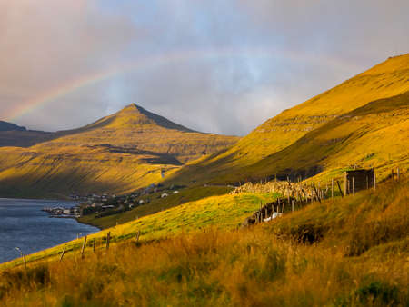 Beautiful view with the rainbow during golden hours for to the peaks of Eysturoy Island. Faroe Islands. Denmark. Northern Europe Stok Fotoğraf