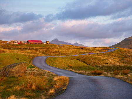A winding dirt road on the Kalsoy Island. The road network in the Faroe Islands is highly developed. Denmark, Northern Europe Stok Fotoğraf