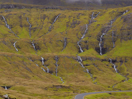 Dozens of small rivulets flowing down the rocks after a rainy day in the Faroe Islands. Denmark, Northern Europe. Stok Fotoğraf