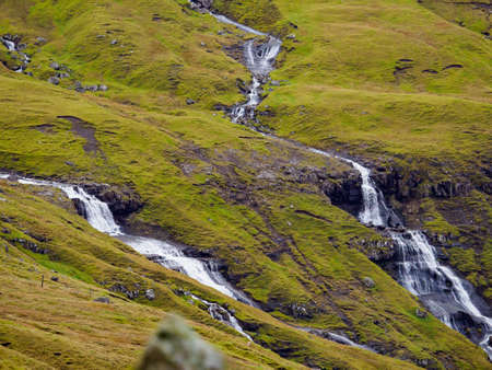 Dozens of small rivulets flowing down the rocks after a rainy day in the Faroe Islands. Denmark, Northern Europe. Stok Fotoğraf - 167055318
