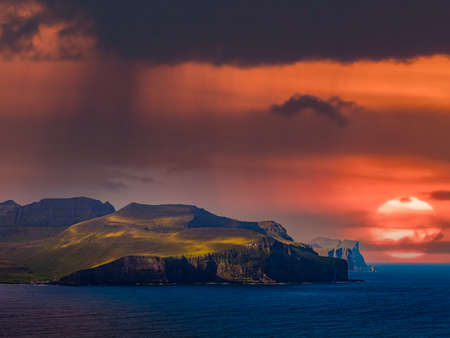 Beautiful sunset view from Kalsoy Island to the peaks of Eysturoy Island. Faroe Islands. Northern Europe