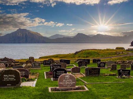 Gjógv, Faroe Islands - Sep, 2020: Small cemetery in Gjogv with the view on fjord and ocean. Northeast tip of the island of Eysturoy, Denmark