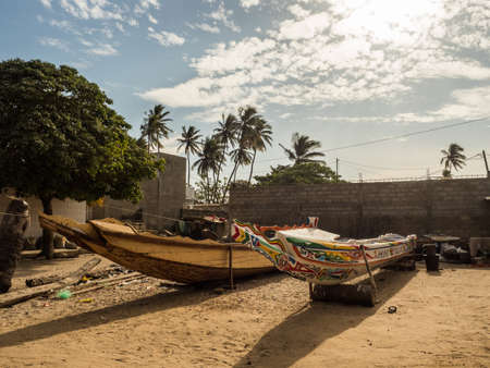 Senegal, Africa - January 24, 2019: Colorful wooden fisher boats standing on the sandy beach in Senegal. Africa