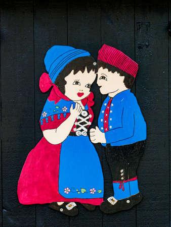 Gjógv, Eysturoy Island - Sep, 2020: Sep 2020: People in traditional Faroese costumes. Figures painted on the doorway of the house in Gjogv, Faroe Island, Denmark, North Europe