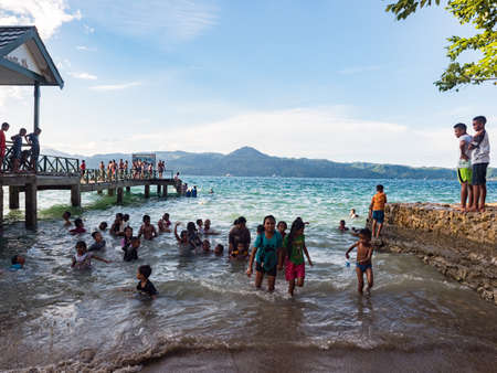 Ambon, Indonesia - February 2018: Many children play and swim in the bathing area at the city beach in the coastal town of Ambon. Ambon Island, Maluku Archipelago, (Moluccas) Indonesia. Asia Stok Fotoğraf - 167313535