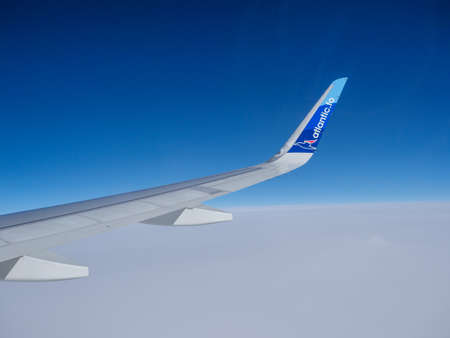Denmark - Oct 2020: Wing of an Atlantic Airways jet on the background of the blue sky during fly from Copenhagen to Faroe Islands. Atlantic is the national airline of the Faroe Islands. North Europe Editöryel
